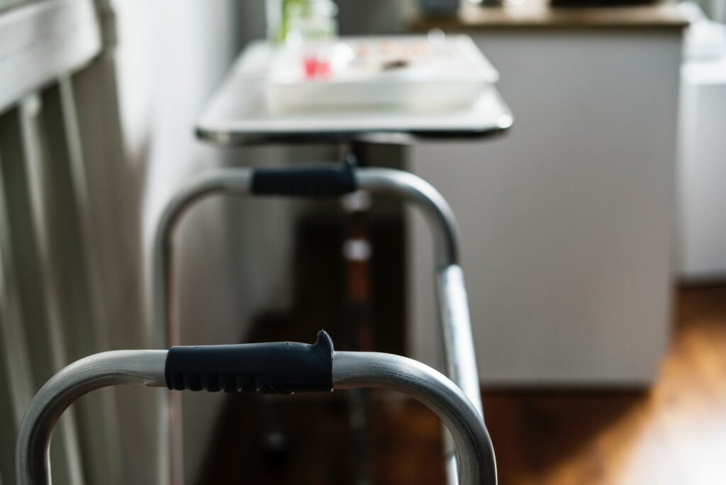 walker handles with black grips, bedside table with medications